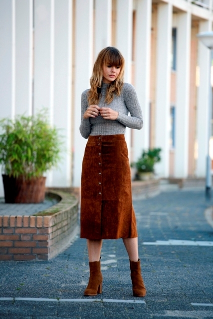 With gray turtleneck and brown suede ankle boots