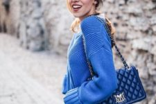 With loose sweater, blue leather bag and jeans