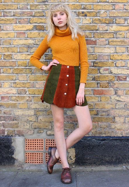 With orange turtleneck sweater and flat lace up boots