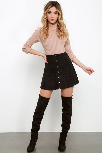 With pastel colored sweater and black over the knee boots