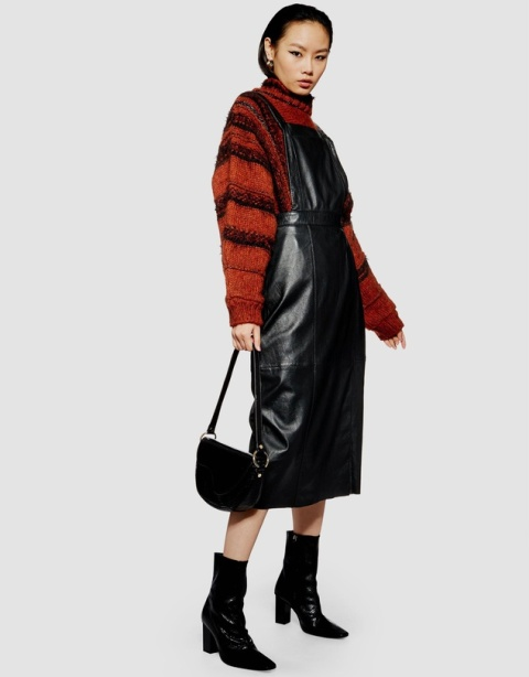 With red and black striped loose sweater, black boots and black half moon bag
