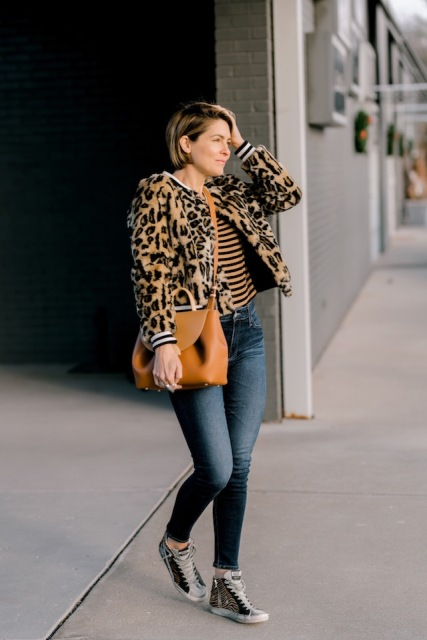 With striped shirt, skinny jeans, brown leather bag and sneakers