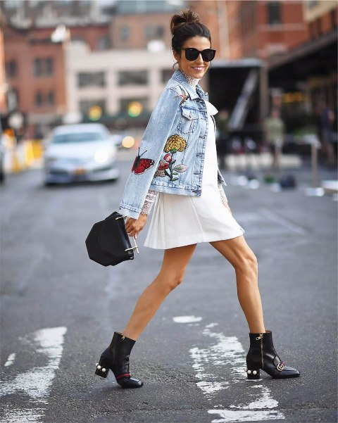 With white mini dress, black small bag and black embellished boots