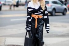 With white shirt, black and white sweater, brown belt, black bag and white shoes