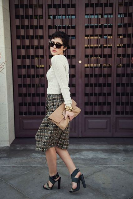 With white sweater, beige leather clutch and black high heels
