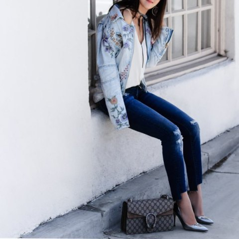 With white top, distressed jeans, printed bag and metallic pumps
