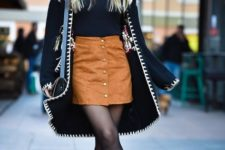With wide brim hat, black shirt, printed cape coat and black lace up boots