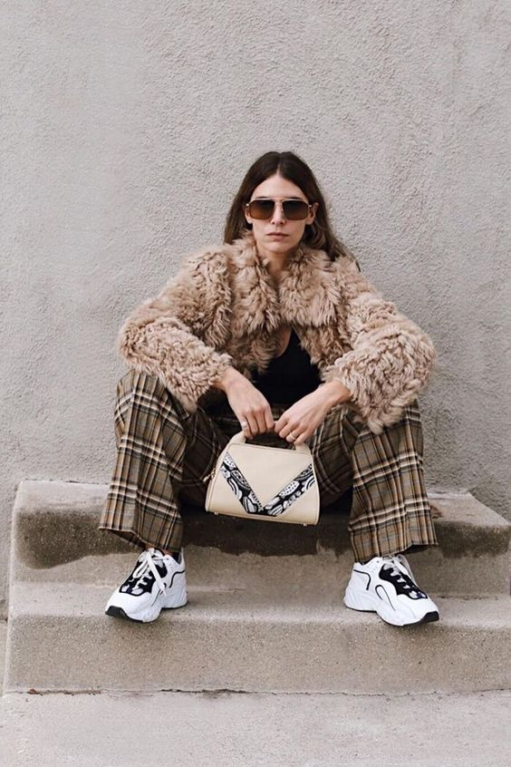 a black top, plaid pants, white trainers, a teddy coat, a printed bag for a unique retro meets sport look