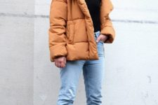 a black turtleneck, blue fringe jeans, blakc sock boots and an amber puffer jacket for a color statement