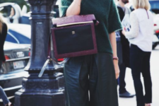 a bold and stylish look with a dark green sweater with short sleeves, black leather culottes, black shoes and a purple bag