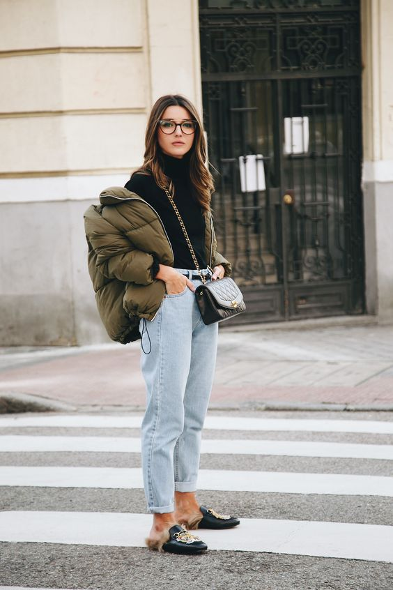a bold look with a black turtleneck, whitewashed jeans, an olive green cropped puffer jacket and faux fur mules