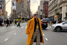 a bold outfit with cropped plaid pants, a yellow tee, a black blazer, black shoes and a yellow coat