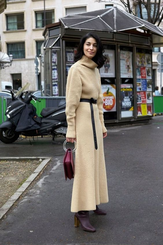 a buttermilk midi knit dress with a turtleneck, long sleeves, a black sash, a burgundy bag and purple boots