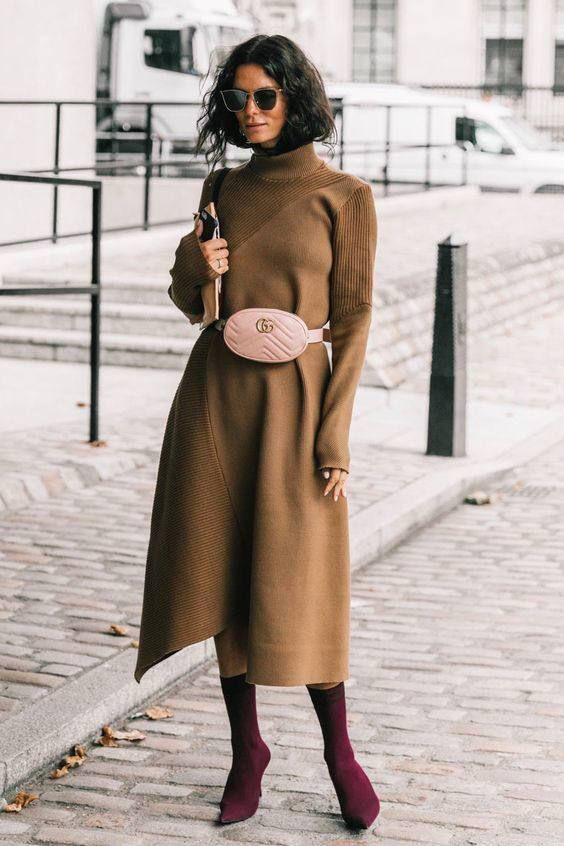 a camel A-line midi knit dress with a turtleneck, long sleeves, a blush waist bag and purple sock boots