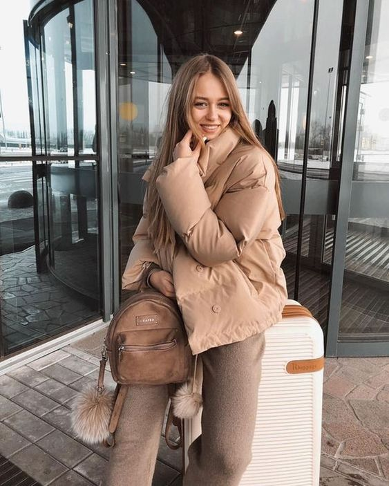 a camel outfit with pants, short puffer jacket, a brown leather backpack for a comfy travel look