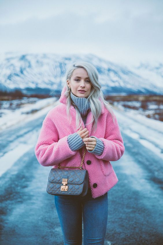 a chic and comfy winter look with a grey sweater, blue jeans, a pink faux fur coat and a grey studded box bag