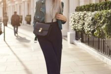 a chic outfit with a grey turtleneck, navy cropped pants, white shoes, a green leather jacket and a black box bag