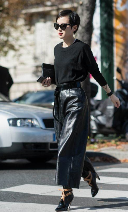 a chic total black look with black leather culottes, black booties with belts, a black jumper and a clutch