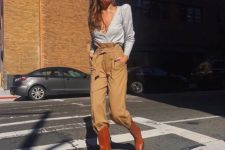 a daring look with a grey blouse, beige high waisted pants tucked into rust-colored cowboy boots