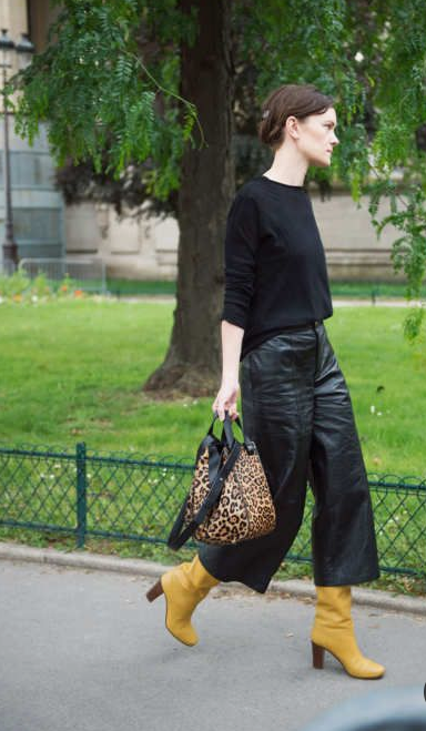 a fall look with a black jumper, blakc leather culottes, mustard boots, an animal print bag
