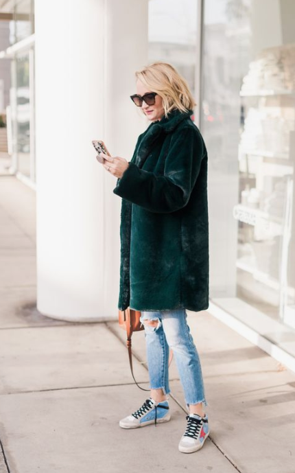 a forest green faux fur coat will add a bold touch of color and a trendy fele to the look