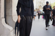 a gorgeous total black look with a sweater, a scarf, leather culottes, a bag, a hat and printed boots
