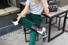 a grey tee, emerald velvet pants and black and white cowboy boots for a bold touch