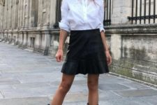 a monochromatic outfit with a white shirt, a black skirt and black cowboy boots to spruce up the look