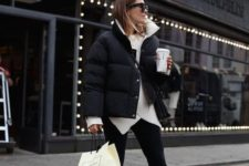 a monochromatic outfit with black pants, a white asymmetrical sweater, white sneakers and a cropped black puffer  jacket