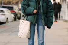 a retro-inspired look with a printed sweatshirt, blue straight jeans, white boots and a bag plus a forest green puffer jacket