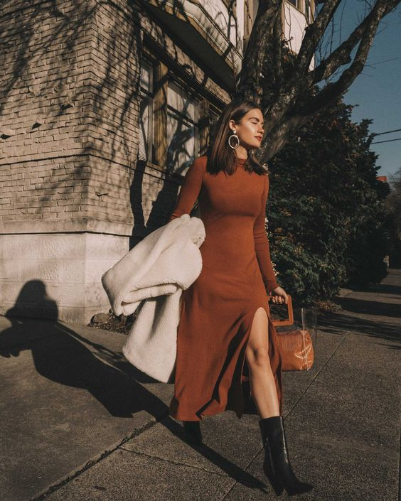 a rust midi A line knit dress with long sleeves, a slit, a turtleneck, black cowboy boots and a white faux fur coat