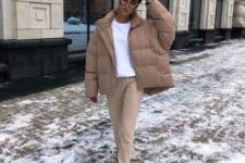 a simple outfit with a white tee, camel pants, black boots, a camel puffer jacket for a cold day