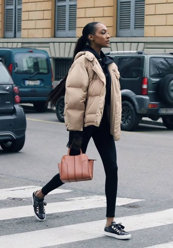 a sporty look with black leggings, a black hoodie, black sneakers and a tan puffer jacket plus an amber bag
