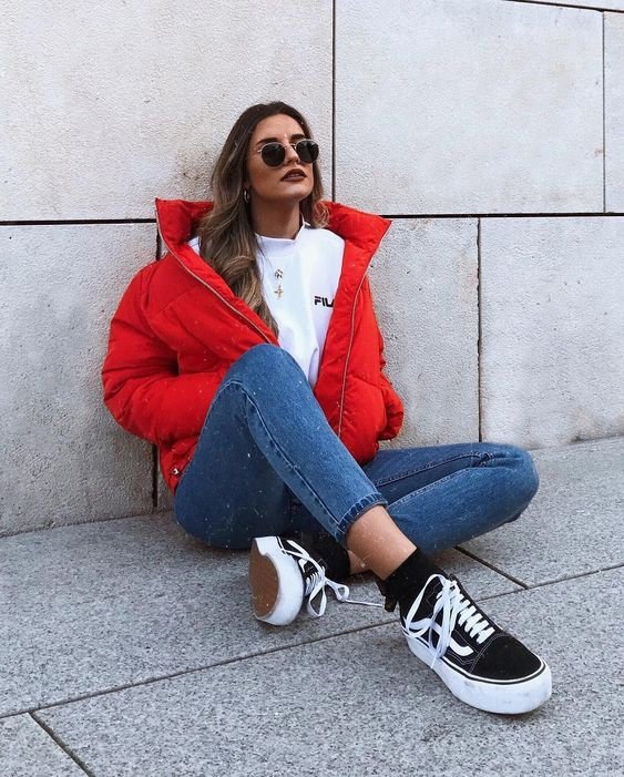a sporty outfit with a white tee, blue skinnies, a red puffer jacket and black sneakers and socks