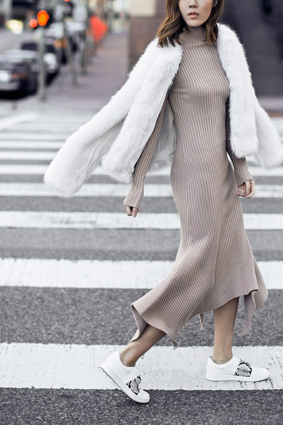 a tan A line midi dress with an asymmetrical skirt, long sleeves and a turtleneck, snake print shoes and a faux fur coat