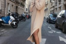 a tan midi knit dress with a side slit and long sleeves plus white trainers