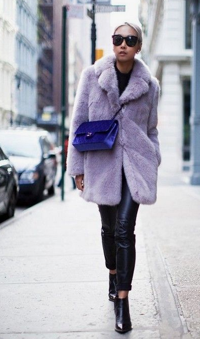 a total black look is spruced up with a lavender short faux fur coat and a bright purple crossbody bag