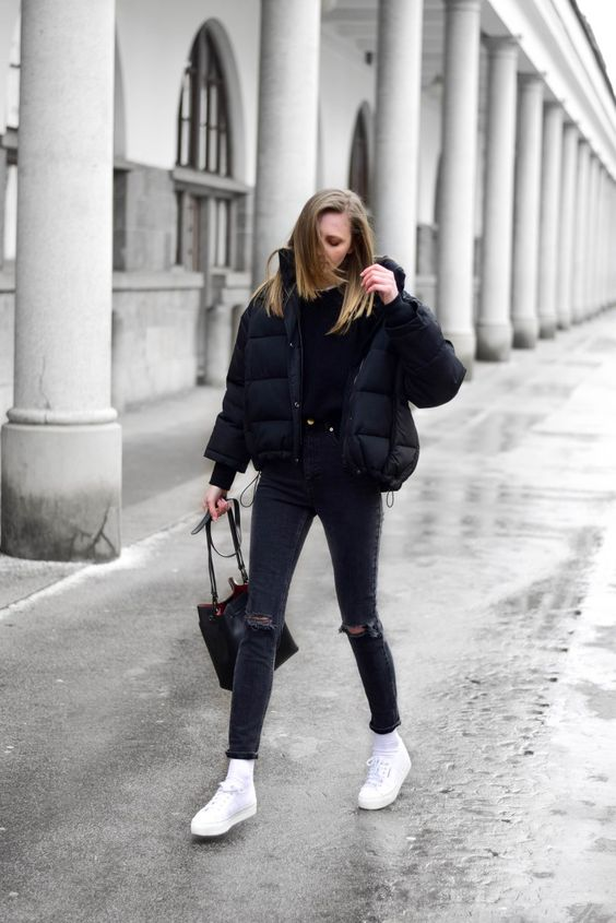 a total black look with a tee, ripped jeans, a cropped puffer jacket, white sneakers and socks