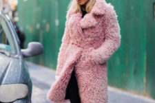 a total black look with heeled booties and a fun pink knee faux fur coat for a touch of tender color in the look