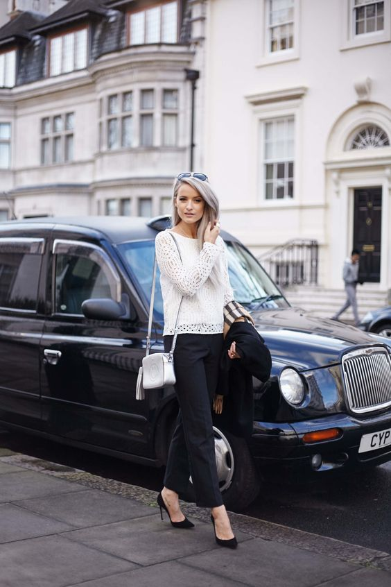 a white lace top, black pants, blakc heels, a black blazer and a white box bag with a smile