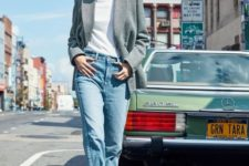 a white turtleneck, blue jeans, a grey oversized blazer and brown and white cowboy boots