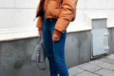 an amber puffer jacket, blue skinny jeans with a raw hem, rust-colored sock boots and a grey bag