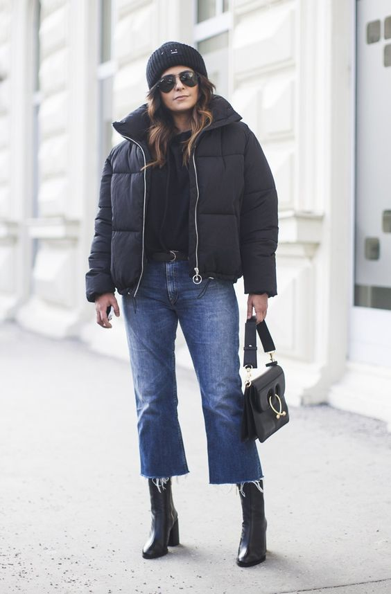 an edgy look with a black top, blue straight jeans, black boots, an oversized black puffer jacket and a black bag