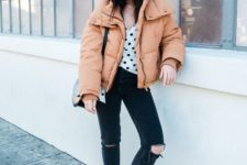 an oversized peachy cropped puffer jacket, a polka dot top, black ripped jeans, white sneakers and a black bag