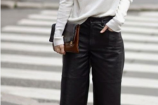 an oversized white cashmere sweater, black leather culottes, black suede booties and a two tone clutch