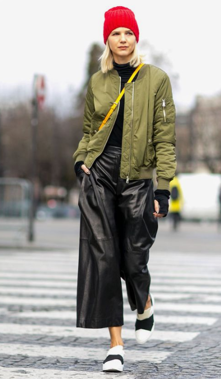 black leather culottes, a black turtleneck, black and white flats, an olive green bomber jacket and a red beanie