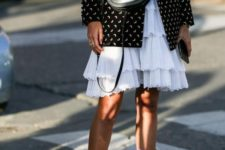 white embroidered cowboy boots, a white ruffled knee dress, a black printed blazer and a black bag
