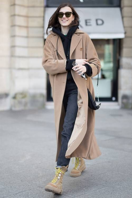 a black hoodie and jeans, a tan midi coat and tan hiking boots, a black bag for a sporty look