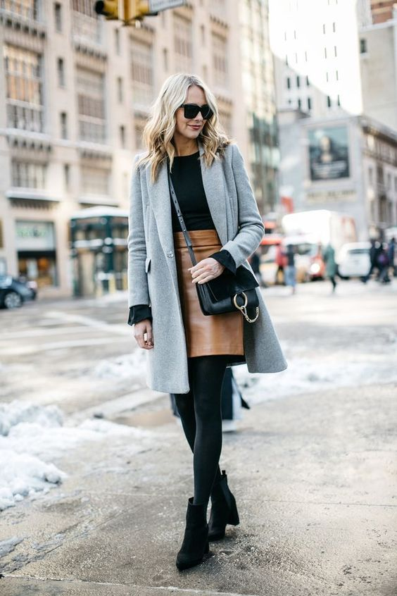 a black jumper, an amber leather mini, black boots and a grey coat for a chic look