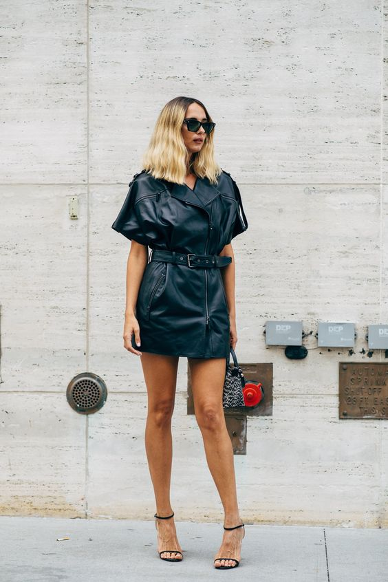 a black leather mini dress styled as a moto jacket, black shoes and an animal print bag